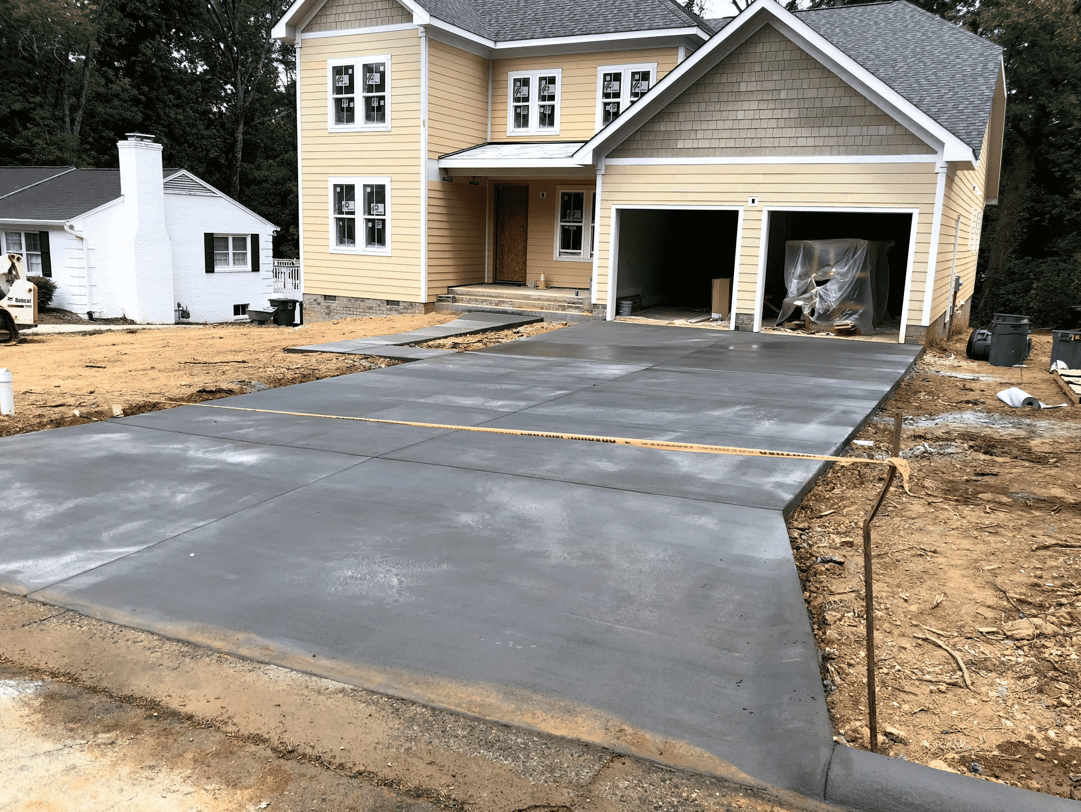 Concrete Driveway and Yellow House
