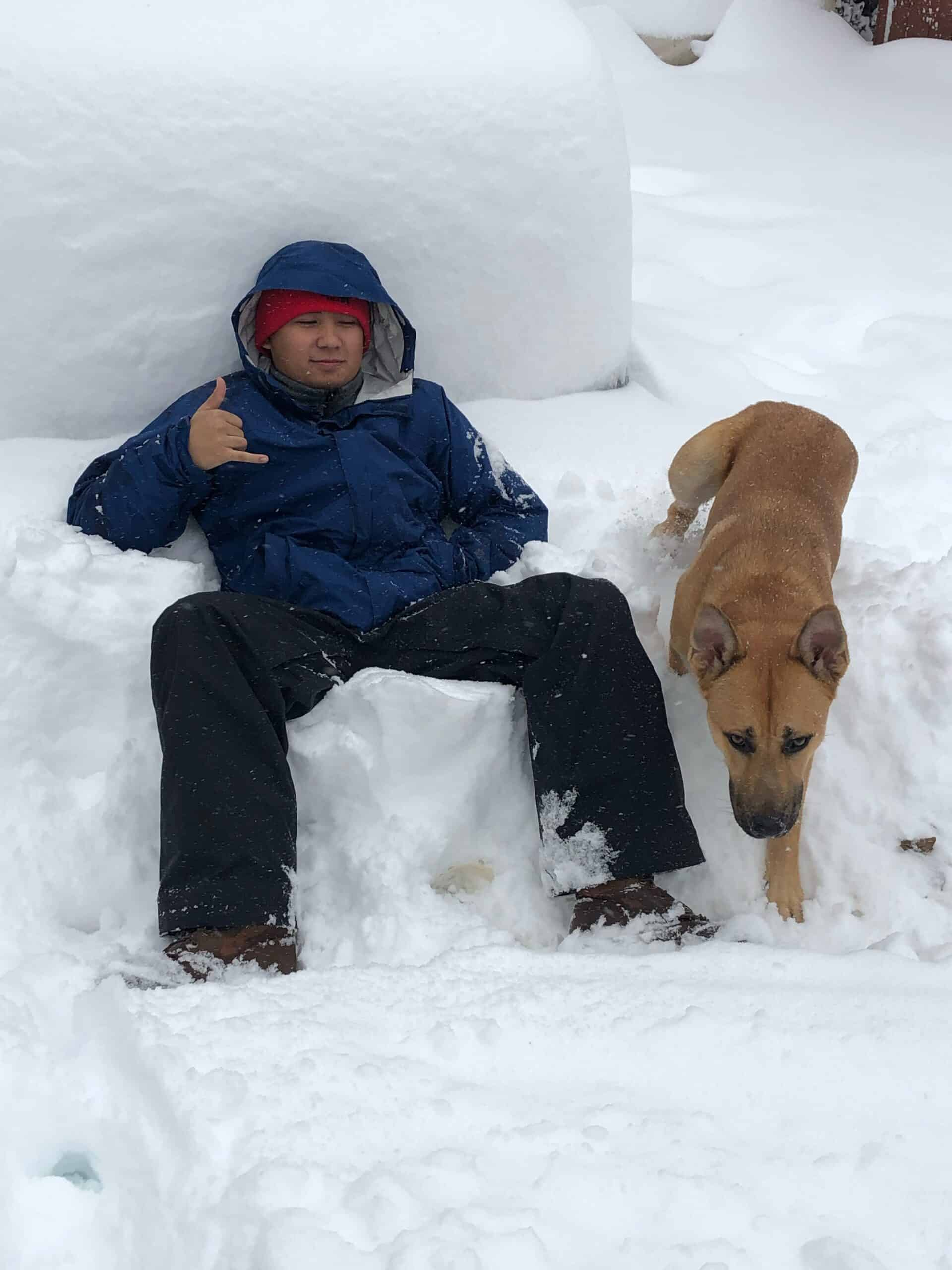 Man and Dog Sitting in the Snow